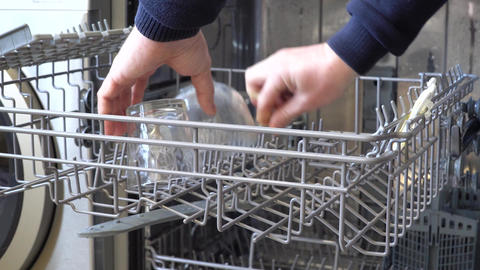 Close-up hands are loading the dishwasher with graceful glasses. Household Live Action
