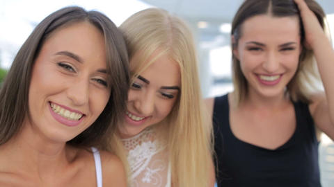 Three beautiful young girls make selfie, girls make a photo using a smartphone Live Action