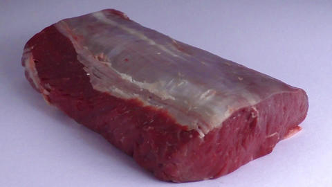 Piece of raw roast beef over white background Live Action