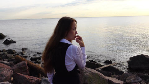 Pensive woman sit on bay shore, camera pan to futuristic tower construction site Footage