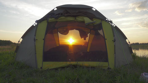 The setting sun shines through camping tent Footage