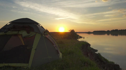 Camping tent, standing on river bank at sunset Footage