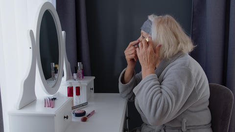 Old senior woman grandmother taking care of skin near eyes and wrinkles, putting Live Action