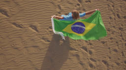 Woman with Brazilian flag waving in the wind, aerial view Footage