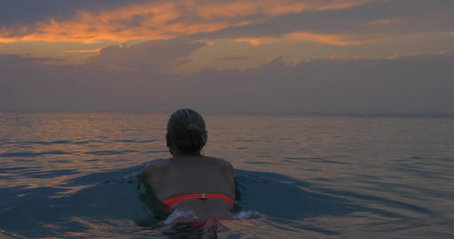 Young woman swims away in the sea at sunset, magical view of evening cloudy sky  Footage