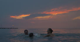 At sunset mother, father with their son swimming in sea of city Perea, Greece Footage
