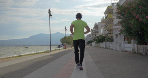 Young man in headphones runs on road of city Perea, Greece Footage