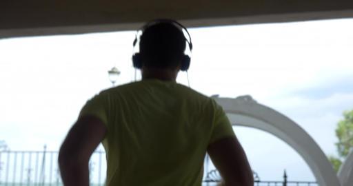 Young man in headphones runs through alley of city Perea, Greece Footage