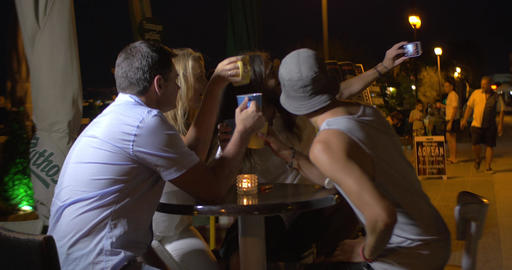 Cheerful group of friends sitting in the evening in the street cafe. All clink m Footage