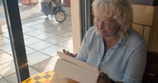 Mature woman sitting in a cafe and enjoys her tablet., outside the window the su Footage