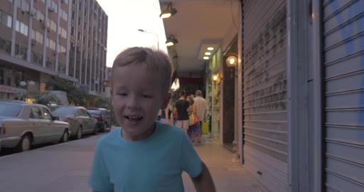 Little boy runs along a busy street of Thessaloniki, Greece Footage