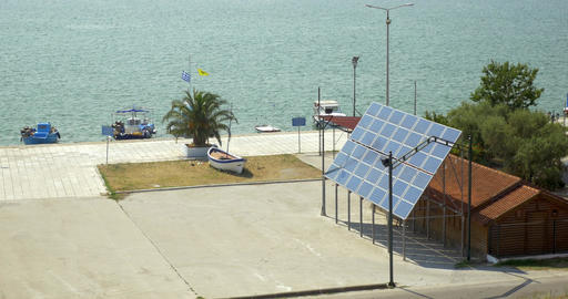 Solar panels are fixed next to the house, in the background is a calm sea Footage