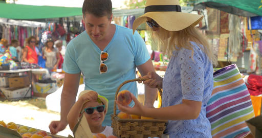 Family choosing peach and speaking with smile on outdoor market Thessaloniki, Gr Footage