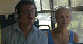 Young couple listening to music on headphones during the bus ride, they dance to Footage