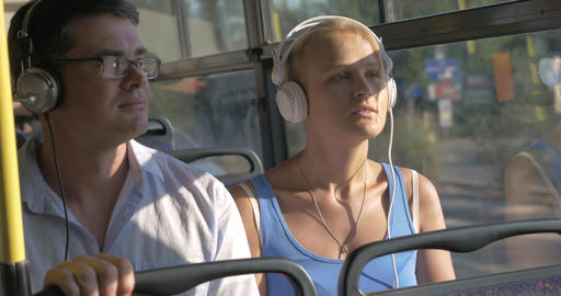 Woman and man listening music in headset during bus trip Footage