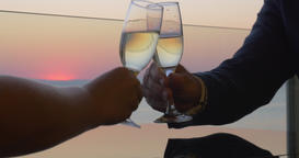 Woman and man hands are clinking glasses of champagne on sunset sea background,  Footage
