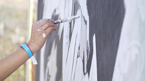 The artist's hand paints the wall painting with a brush and paints Street art Live Action