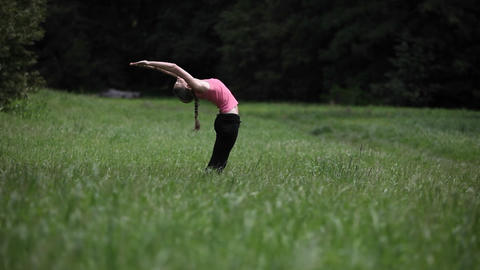 A young woman does yoga exercises in a field of grass Stock Video Footage