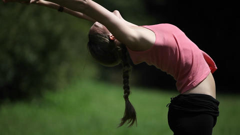 A woman performs the various postures of the sun salutation Stock Video Footage
