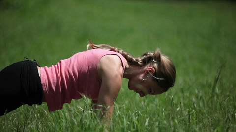 A woman performs the various postures of the sun salutation Footage