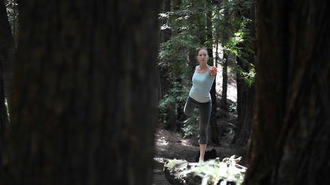 A woman stretches in the midst of a forested area Footage