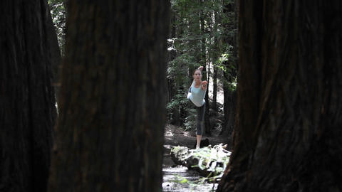 A woman stretches in the midst of a forested area Stock Video Footage