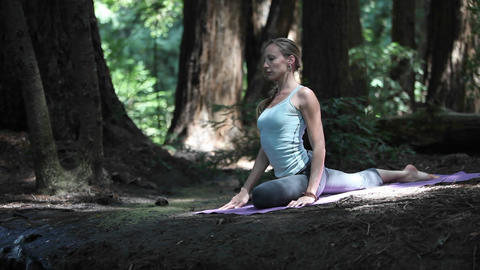 Young woman performing yoga stretches in the forest Stock Video Footage