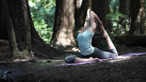 A young woman does yoga exercises on a mat in the woods Stock Video Footage