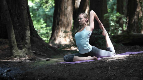 A young woman does yoga exercises on a mat in the woods Footage