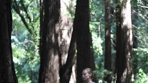 A woman does yoga exercises on a mat in the woods Footage