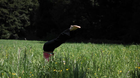 A woman doing yoga in a field falls over from her head stand Stock Video Footage