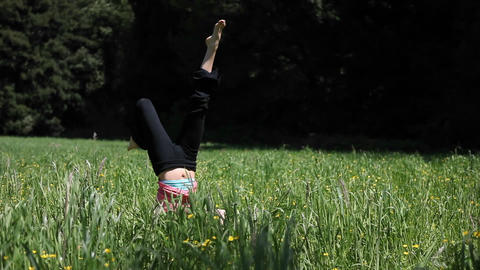 A woman doing yoga in a field falls over from her head stand Footage