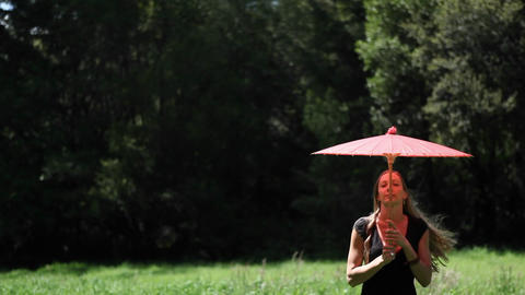 A woman with an umbrella walks in a field Footage