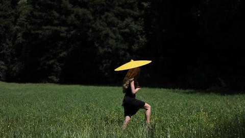 A young woman walks through a field carrying a parasol Stock Video Footage