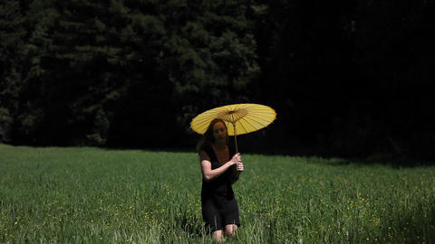 A young woman walks through a grassy field carrying a yellow parasol Footage