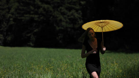 A young woman walks through a grassy field carrying a... Stock Video Footage