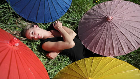A woman lays on her back in a grassy field surrounded my different colored umbrellas Footage