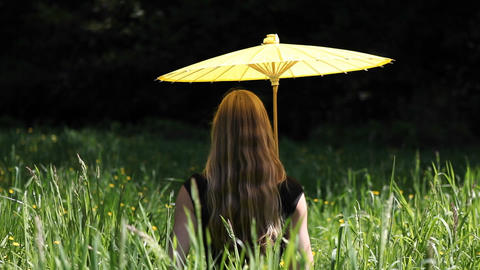 A woman sits in the grass with a yellow umbrella Stock Video Footage