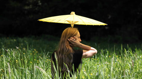 A woman with an umbrella sits in a field Footage