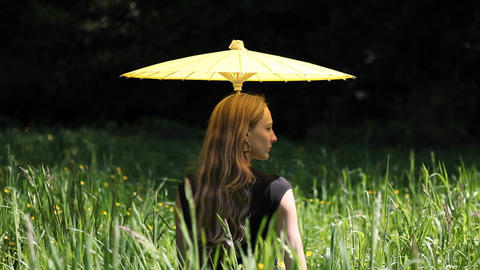 A woman with an umbrella sits in a field Stock Video Footage