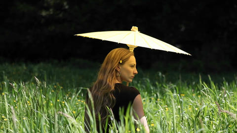 A young woman with an umbrella standing in tall grass Stock Video Footage