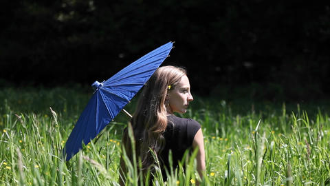 A woman sits in a grassy field holding a blue umbrella Stock Video Footage