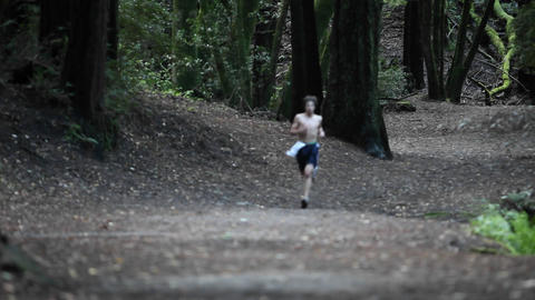 A shirt-less man runs in a forested area Stock Video Footage