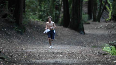 A shirt-less man runs in a forested area Footage