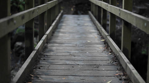Person wearing socks (but no shoes) runs over wooden bridge Stock Video Footage
