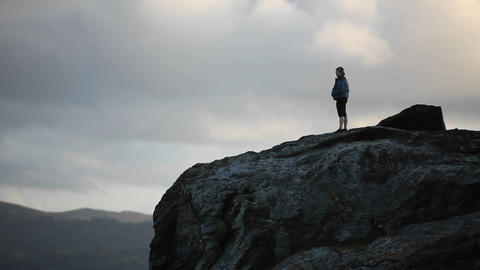 A woman looks out into the distance on a high cliff Stock Video Footage