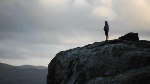 A woman looks out into the distance on a high cliff Footage