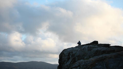 A person sits at the top of a rocky mountain Stock Video Footage