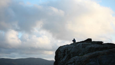 A person sits at the top of a rocky mountain Footage