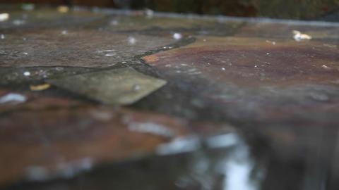 Rain falls on a stone sidewalk Stock Video Footage